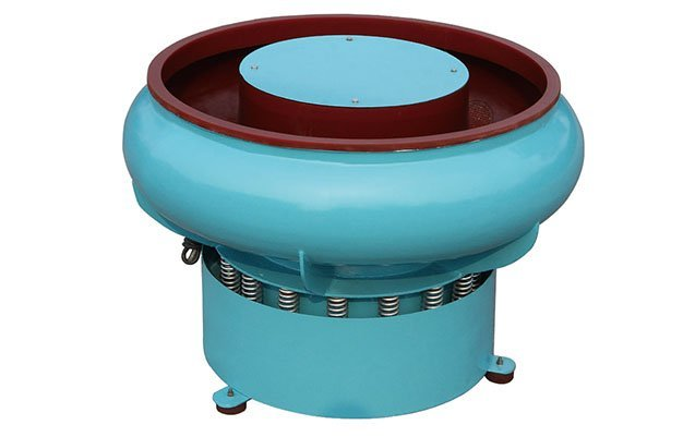 Vibratory finishing machine with curved wall for ball burnishing polishing